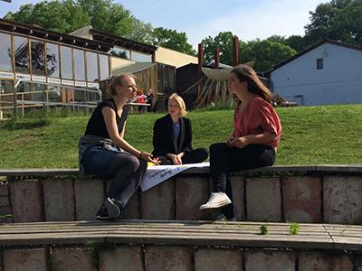 Photo von drei Trainees in Diskussion mit einem Flipchart zwischensich.