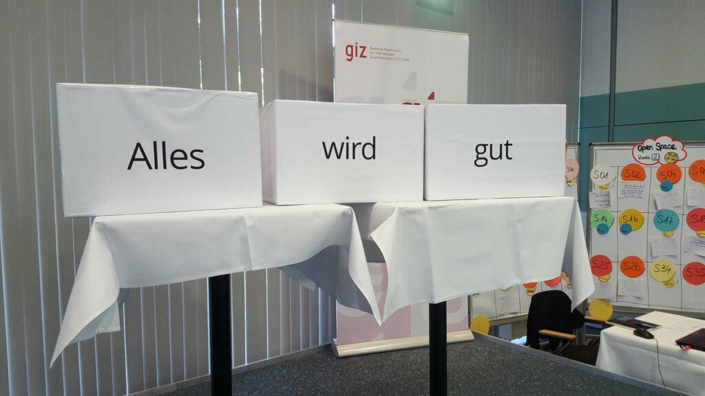 """Photo einer Ausstellung auf einer Konferenz mit Kisten mit der Beschriftung """"alles wird gut""""."""