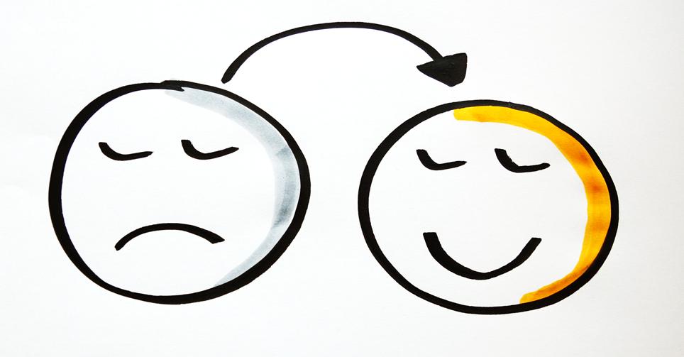 Photo von zwei gemalten Gesichter, das eine traurig, das andere lächelnd, mit einem Pfeil vom traurigen zum lächelnden Gesicht.