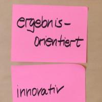 Photo von zwei pinken Post-Its auf denen ergebnisorientiert und innovativ mit schwarzem Filzer geschrieben ist.
