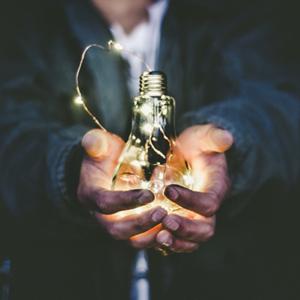 Photo von zwei Händen, die eine leuchtende Glühbrine halten.