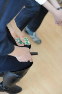 Foto von einer Person welche man nur unterhalb dem Kopf sieht. Die Person sitz und hält grüne Klebepunkte in der Hand