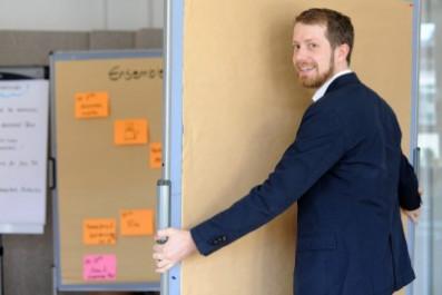 Bild von einem Berater von denkmodell, der eine Pinnwand trägt und ins Bild lächelt