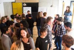 Foto von vielen Menschen in einem Raum die sich immer zu zweit gegenüberstehen (Gruppenarbeit)