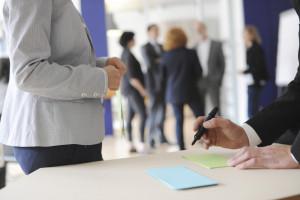 Bild von 4 Personen die sich unterhalten, im Vordergrund ist der Oberkörper einer Person zu sehen, die vor einem Tisch steht und darauf liegen bunte Post Its welche von einer anderen Person beschrieben werden