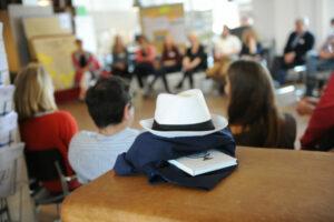 Bild von unserem Büro mit einem Stuhlkreis, indem Teilnehmer sitzen. Im Vordergrund sieht man eine Jacke zusammengefaltet worauf ein Hut liegt und dazwischen ein Buch