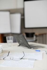 Bild von einem Schreibtisch mit einem Laptop, Papieren einem Wasserglas und einer Brille. Im Hintergrund sind Flipcharts zu sehen