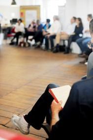 Foto von mehreren Menschen, die in einem Razum sitzen und ein Zettel vor sich haben