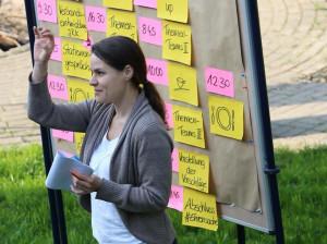 Foto von einer Trainerin die vor einer Pinnwand steht