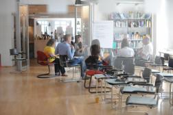 Foto von unserem Büro, zusehen sind Menschen die auf eine Flip Chart schauen und sich unterhalten