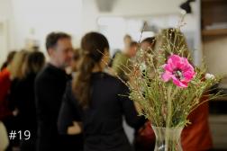 Bild auf dem im Vordergrund Blumen zu sehen sind, und im Hintergrund Leute die sich miteinander austauschen