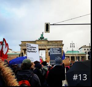 Foto auf dem das Brandenburger Tor zusehen ist, mit Menschen die Plakate zum Thema Klimastreik in die Luft heben