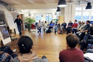 Foto von unserem Büro indem alle Teilnehmer der OE Ausbildung in einem Stuhlkreis sitzen und Vorne ist der Trainer zu sehen