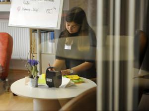 Foto mit einer Frau, die am Tisch sitzt und etwas aufschreibt