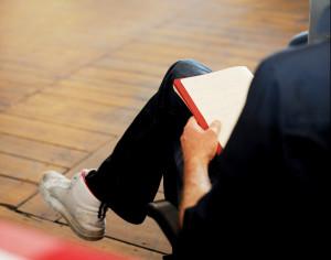 Foto auf dem man einen Körper von einer Person sieht. Die Person sitzt mit verschrenkten Beinen und hat ein Buch auf dem Schoß