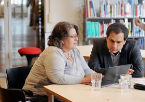 Foto mit einer Frau und einem Mann, die am Tisch sitzen und auf einen Laptop gucken