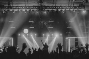 Foto in schwarz weiß von einem Konzert mit Blick auf die Bühne, wo ein Mann steht der seine Hand nach oben hebt