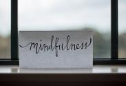 """Foto von einem Zettel mit der Aufschrift """"mindfulness"""" und im Hitergrund sieht man ein Fenster"""