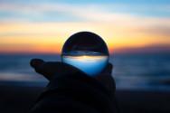 Foto mit einer Hand die eine Glaskugel hält und im Hintergrund ist das Meer und ein orange blauer Sonnenuntergang