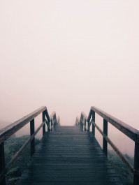Foto mit einer langen Holztreppe, die im weißen nebel verschwindet