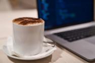 Foto mit einer Tasse Kaffee und daneben steht ein Laptop