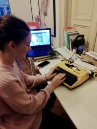 Foto mit einer Frau, die an einer Schreibmaschine schreibt, an Ihrem Schreibtisch sitzt und hinten steht Ihr Laptop