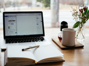 Foto mit einem Laptop, ein Buch darauf ein Stift ist im Vordergrund und eine Tasse steht auf dem Schreibtisch