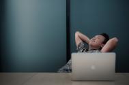 Foto von Mann vor dem Laptop der mit verschränkten armen über dem Kopf nach oben schaut