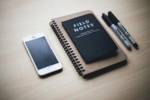 Foto mit einem Handy, einem Notizbuch und stiften
