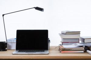 Foto mit einem Ordentlichen Schreibtich, mit einem aufgeklappten Laptop, einer Schreibtischlampe und Büchern