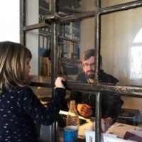 Foto mit einem Mann der arbeitet und am Fenster steht ein Kind und guckt Ihn an