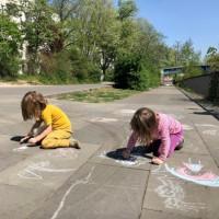 Foto von zwei kindern die aus der Straße mit Kreide malen