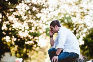 Foto mit einem Mann, der draußen ist, sich hin gehockt hat und seinen kopf festhält