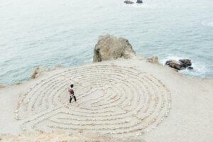Foto vom Meer mit strand, darauf ist ein Musteraus Steinen und ein Mensch läuft darin