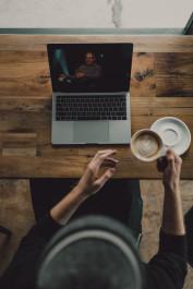 Foto mit einer Person vor einem Laptop und einer Kaffeetasse in der Hand