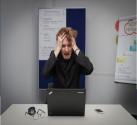 Foto von einem Mann, der vor einem Laptop sitzt und sich mit deinem Händen an den Kopf fasst