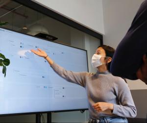Foto von einer Frau, die an einem großen Bildschirm steht und auf eine Stelle zeigt