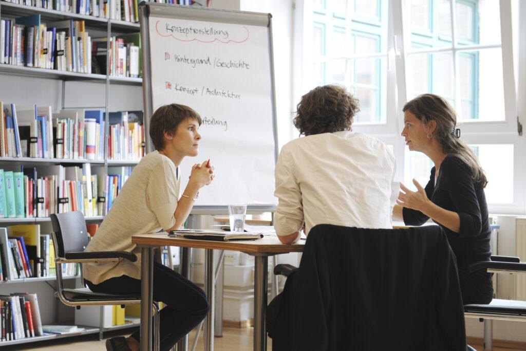 Drei Menschen sitzen um einen Tisch und diskutieren.