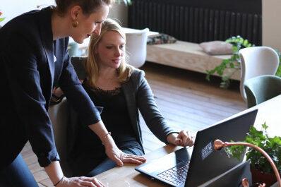 Foto von zwei Frauen, welche auf einen Laptop gucken