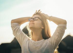 Foto von einer entspannten Frau, die Ihre Arme hinter dem Kopf verschrenkt