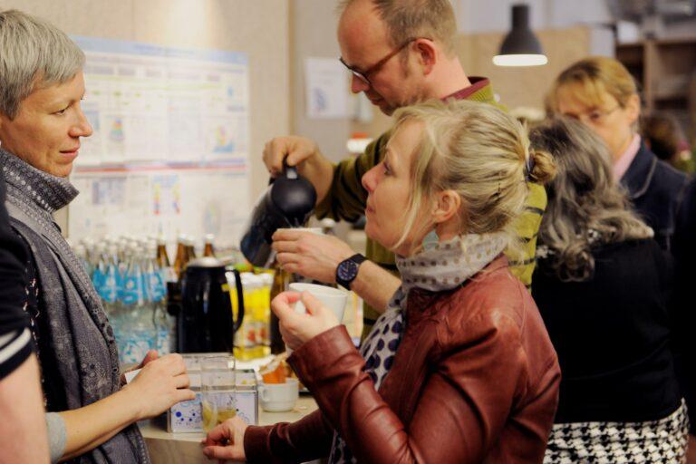 Foto von zwei Personen vor einem Getränkebuffet, die sich unterhalten.