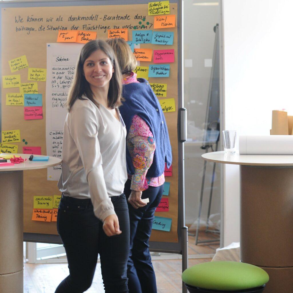 Foto eines Trainingsettings mit einer lachenden Frau sowie Workshopmaterial bei denkmodell