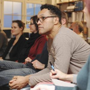 Foto von fünf Personen die nebeneinander sitzen und zuhören