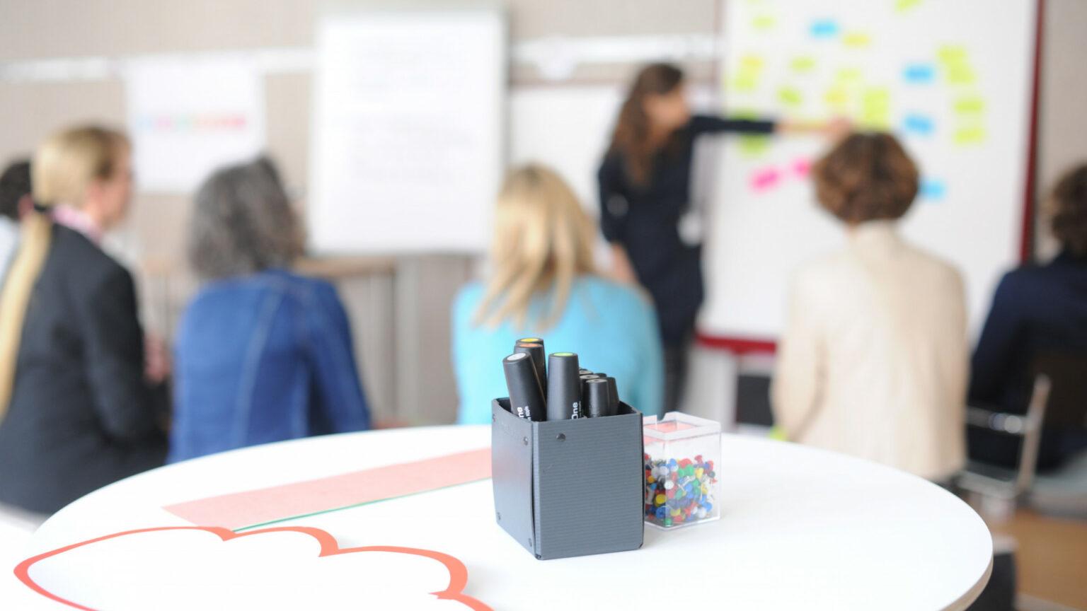 Foto einer Stiftebox mit Markern auf einem Tisch, im Hintergrund eine Gruppe von sitzenden Menschen und einer stehenden Person, die an einer Flipchart etwas erklärt als Symbolbild für den Aufbaukurs Moderation & Facilitation.