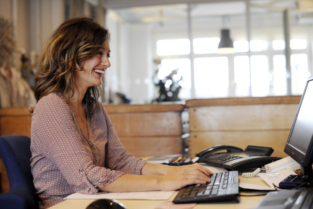 Foto einer Frau am Schreibtisch, die auf einen Bildschirm schaut.