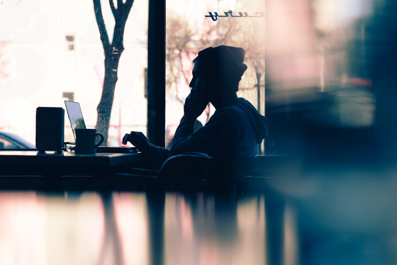 Foto einer Perrson im Gegenlicht, die am Laptop sitzt als Symbolbild für das Training Teams virtuell führen