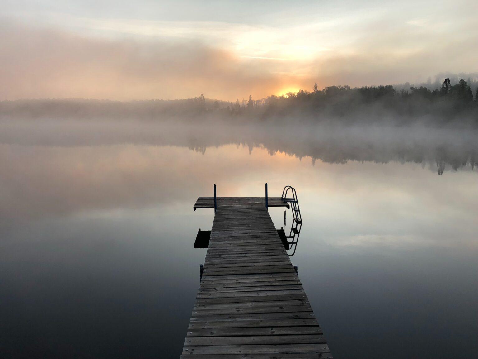 Foto eines Sees mit einem Steg, am Horizont geht vor einem Wald die Sonne im Nebel unter als Symbolfoto für das Training Mindful Self-Leadership