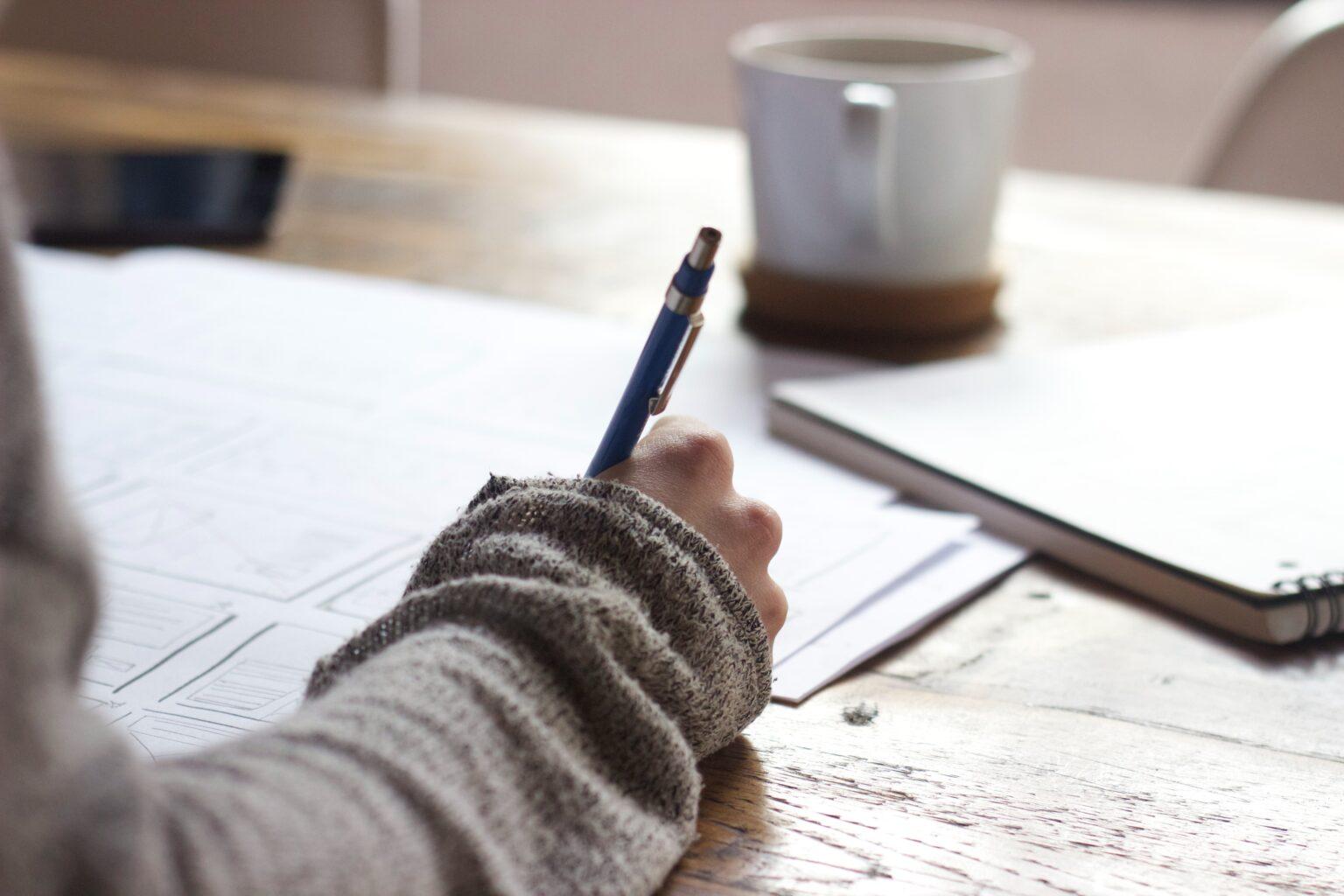 Foto eines Schreibtisches mit einer Tasse Kaffee und Unterlagen, auf der eine Hand mit einem Stift schreibt als Symbolbild für das Training Projektmanagement.