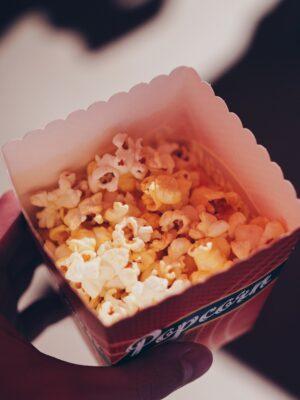 Foto einer Papierpopcorntüte von oben mit knusprigen Popcorn, gehalbte von einer schemenhaften Hand.