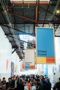 Foto einer Halle einer Großveranstaltung mit Menschenmasse im unteren Teil und großen Schildern im oberen Teil des Fotos.